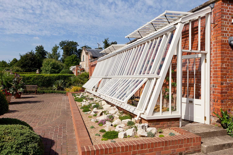 "Et ""lean-to"" drivhus designet som et ferskenhus med en skrånende side i offwhite"