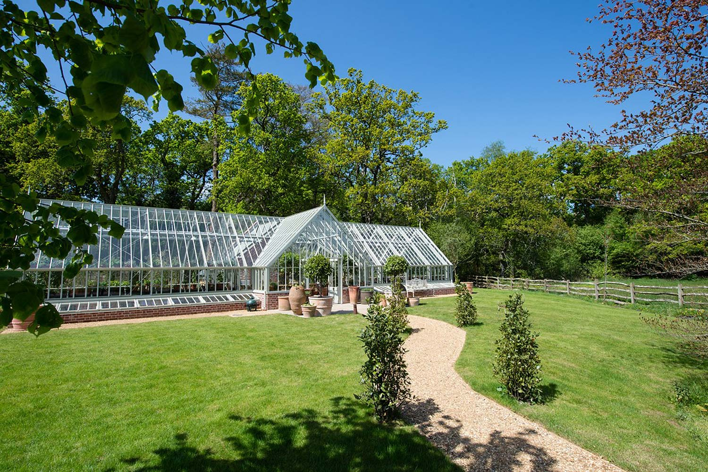 Et frittstående drivhus i Woodsage, korsformet med rikelig plass til dyrking i hver sone